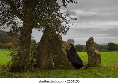 Woman or witch in black cape walking around a group of menhirs and a solitary tree