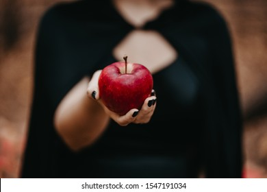 Woman as witch in black offers red apple as symbol of temptation, poison. Fairy tale concept, halloween, cosplay.