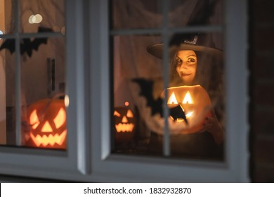 Woman witch carrying a pumpkin for Halloween night - Spooky scene with halloween symbols and signs  - holidays, culture and lifestyle in UK and United States
