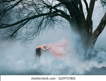 woman witch fly levitating in air spiritually ghost. long pink dress hair waving fluttering wind. Fog autumn spring bare tree backdrop. fantasy magic princess Art photo sleeping beauty lady levitation