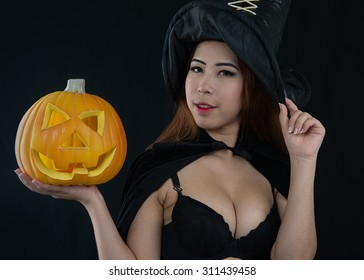 Woman in witch Sexy costume opens carved Halloween pumpkin