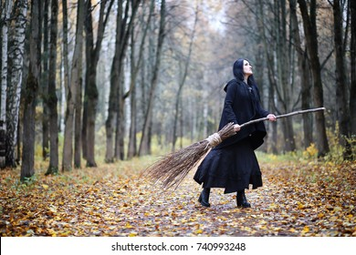 A woman in a witch suit in a dense forest on a ritual