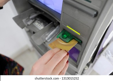 A woman withdraws money from the ATM with credit card and pin code