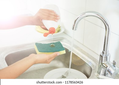 woman without gloves or washing dishes with a sponge. gel and foam for washing dishes. dirty dishes in the kitchen.
