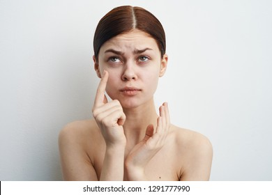 woman without makeup points finger at the eyes