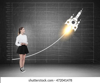 Woman witnessing skyrocket growth on blackboard. Concept of great business planning strategy and success