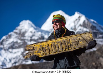 Woman with wooden sing of high elevation, Camping in Nepal