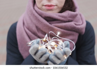 Woman in woolen gloves holding led lights. Holiday spirit and magic