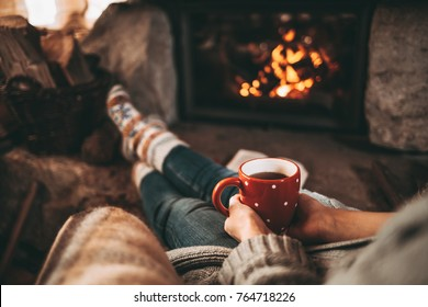Woman in woollen socks by the fireplace. Unrecognisable relaxes by warm fire with a cup of hot drink and warming up her feet in woollen socks. Cozy atmosphere. Winter and Christmas holidays concept.