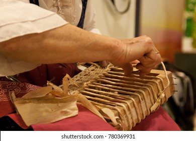Woman at work. Woman is doing a basket with vimini - Shutterstock ID 780369931