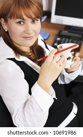Woman at work in the office with morning coffee