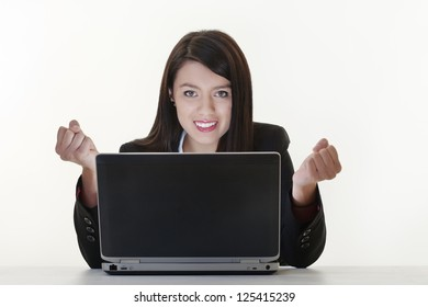 woman at work on a laptop with a light sources  coming from the computer screen looking very happy and overjoyed about something