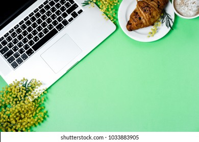 Woman work space with laptop, mimosa flower, croissant, coffee and stationery on a green background. Top view, flat lay.