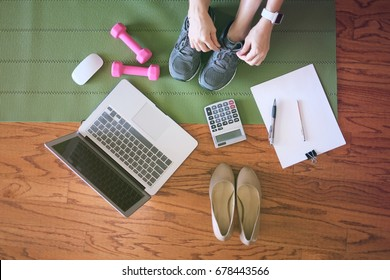 woman work and workout at home for healthy concept and work life balance.  With laptop and workout equipments. top view.