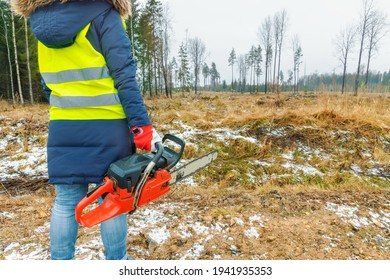 Woman worker with chainsaw in wet winter forest