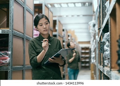 woman worker doing stocktaking of products in cardboard box on shelves in warehouse using clipboard and pen. female staff checking stock in factory stockroom. girl working in storehouse with coworker