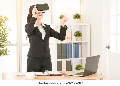 woman worker excited using a VR headset and touch screen on air experiencing virtual reality with pointing gesture at office workplace.
