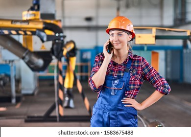 woman worker with Hard Hats at industrial factory looking in phone. Concept lazy worker.