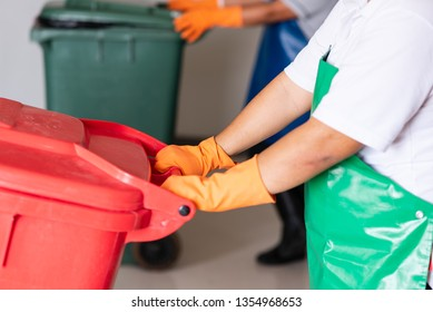 A woman worker holding red bin.Maid and infection waste bin at the indoor public building.Red bin with waste bag on floor in the hospital.Infectious control.