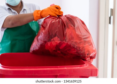 A woman worker holding red garbage bag into recycle bin.Maid and infection waste bin at the indoor public building.Red bin with waste bag on floor in the hospital.Infectious control.