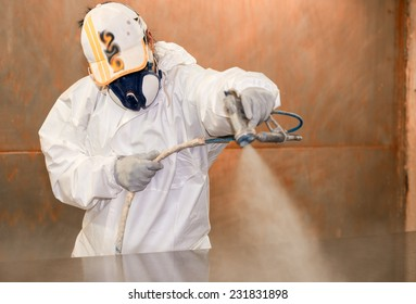 Woman worker painting wooden board with spray.