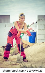 Woman worker using shovel standing on industrial construction site, working hard on house renovation.