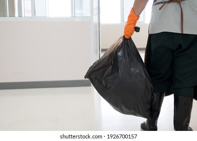 A woman worker wearing orange gloves holding red and black garbage bag into bin.Maid and infection waste bin at the indoor public building.Infectious control.