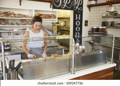 Woman working behind the counter at a sandwich bar