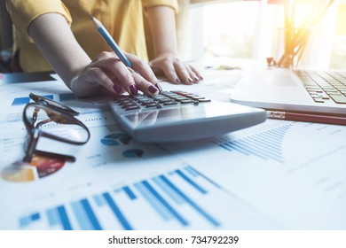 A woman working with calculator and laptop computer for business financial document report, business finance concept
