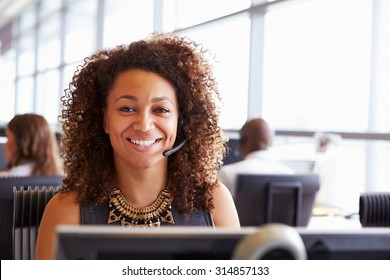 Woman working in a call centre, looking to camera, close-up