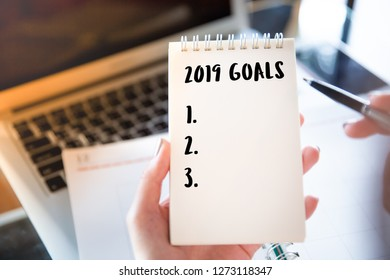 Woman working at coffee shop cafe with a laptop and notepad 2019 goals text and coffee cup on table. Concept of new year future planning business. Business motivation,inspiration concepts