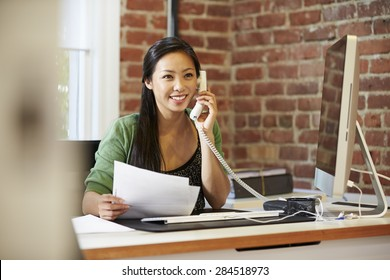 Woman Working At Computer In Contemporary Office