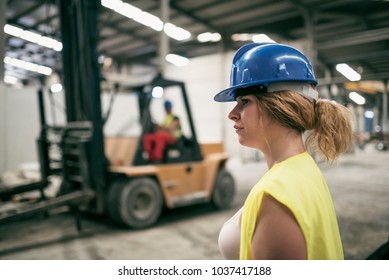 Woman working in construction factory. Man driving forklift in background