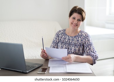 Woman working with documents looking at laptop