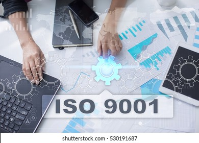 Woman is working with documents, tablet pc and notebook and selecting iso 9001.