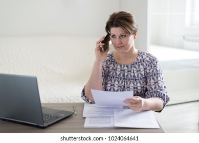 Woman working with documents and talking on phone