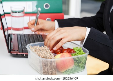 Woman working and eating at office desk
