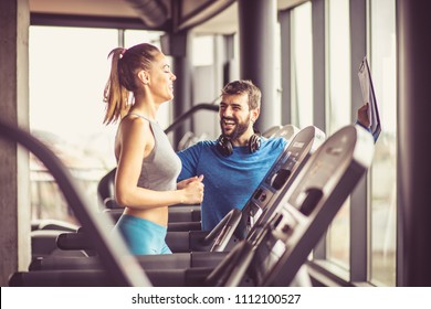Woman working exercise on treadmill. Personal trainer helping her.