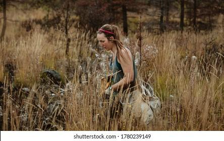 Mujer trabajando en el bosque para plantar árboles nuevos, caminando a través de pasto seco llevando bolsas de plántulas nuevas. Mujer trabajando en plantar árboles forestales.