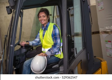 Woman working with a forklift in a warehouse.