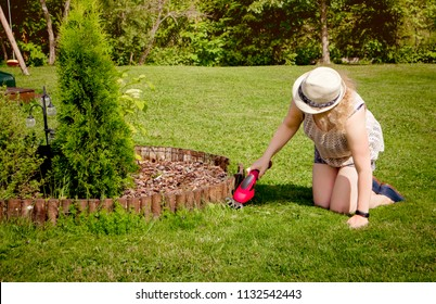 Woman working in garden, shearing too long grass with electric pruning shears, trimming the lawn in the side of the bark mulch covered flower bed.