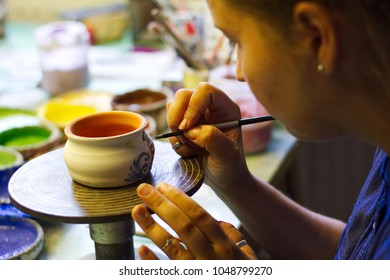 Woman working In her pottery studio. Ceramic workshop. Paint on clay cup in the pottery. Painting in pottery