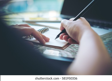 A woman working and holding black pencil and writing on notebook on glass table at outdoor by swimming pool