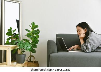 Frauen, die von zu Hause aus mit Laptop-Computer umgeben grünen tropischen Baum, Mensch und Natur, Hauspflanzen wachsen im Wohnzimmer für die Luftreinigung in Innenräumen und häusliche Dekoration.