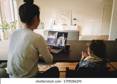 Woman working from home, with her daughter sitting by at the table, having a video conference call. Businesswoman having a video conference call from home.
