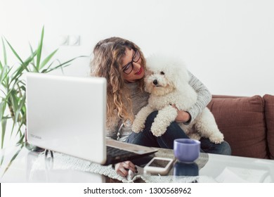 Woman working at home and hugging her puppy