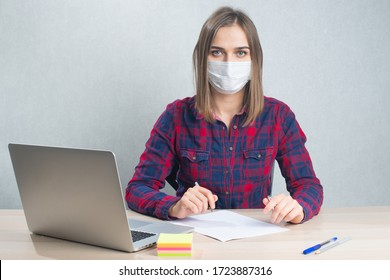 Woman working from home with laptop, wearing protection medical mask