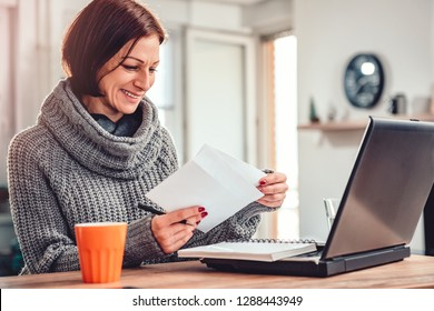 Woman working at home office and opening letter