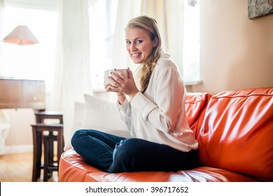 Woman working from home on her relaxing orange couch