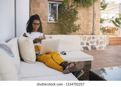 Woman working from home at the yard on her computer and typing on the mobile phone